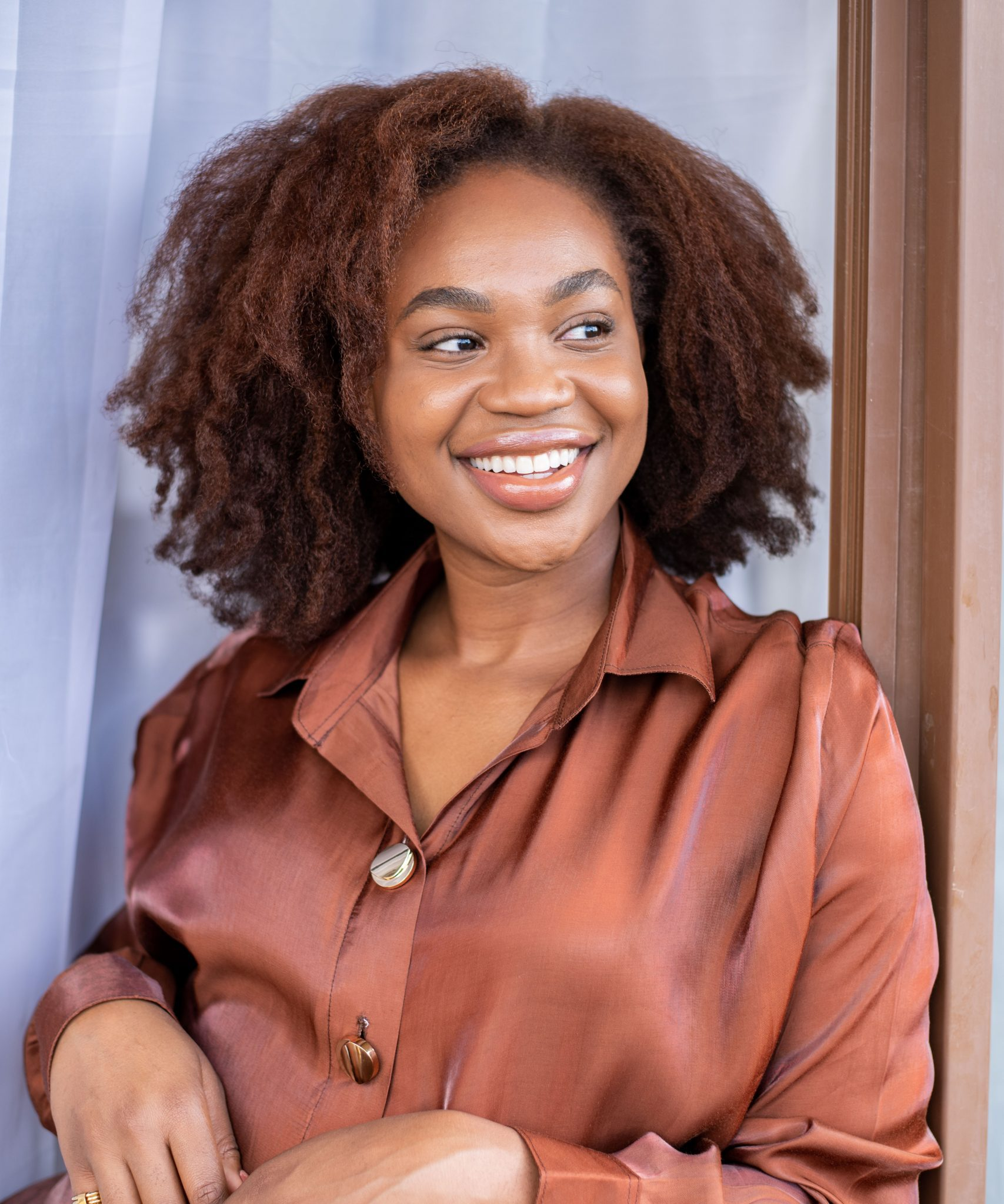 Ijema Kola smiling with afro and brown satin shirt - Earn extra money blog
