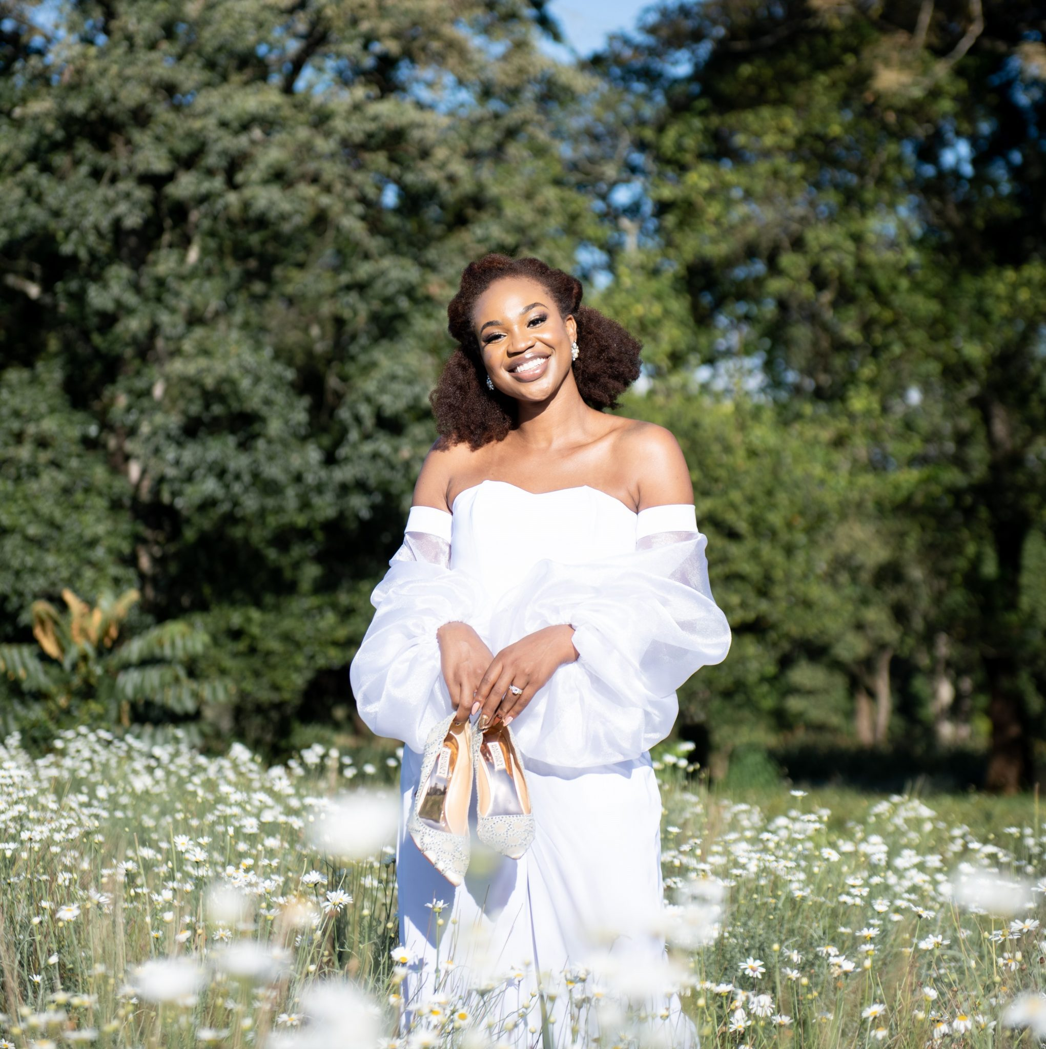 Ijeoma Kola posing in a field of flowers in re-created wedding hairstyle, make-up and outfit