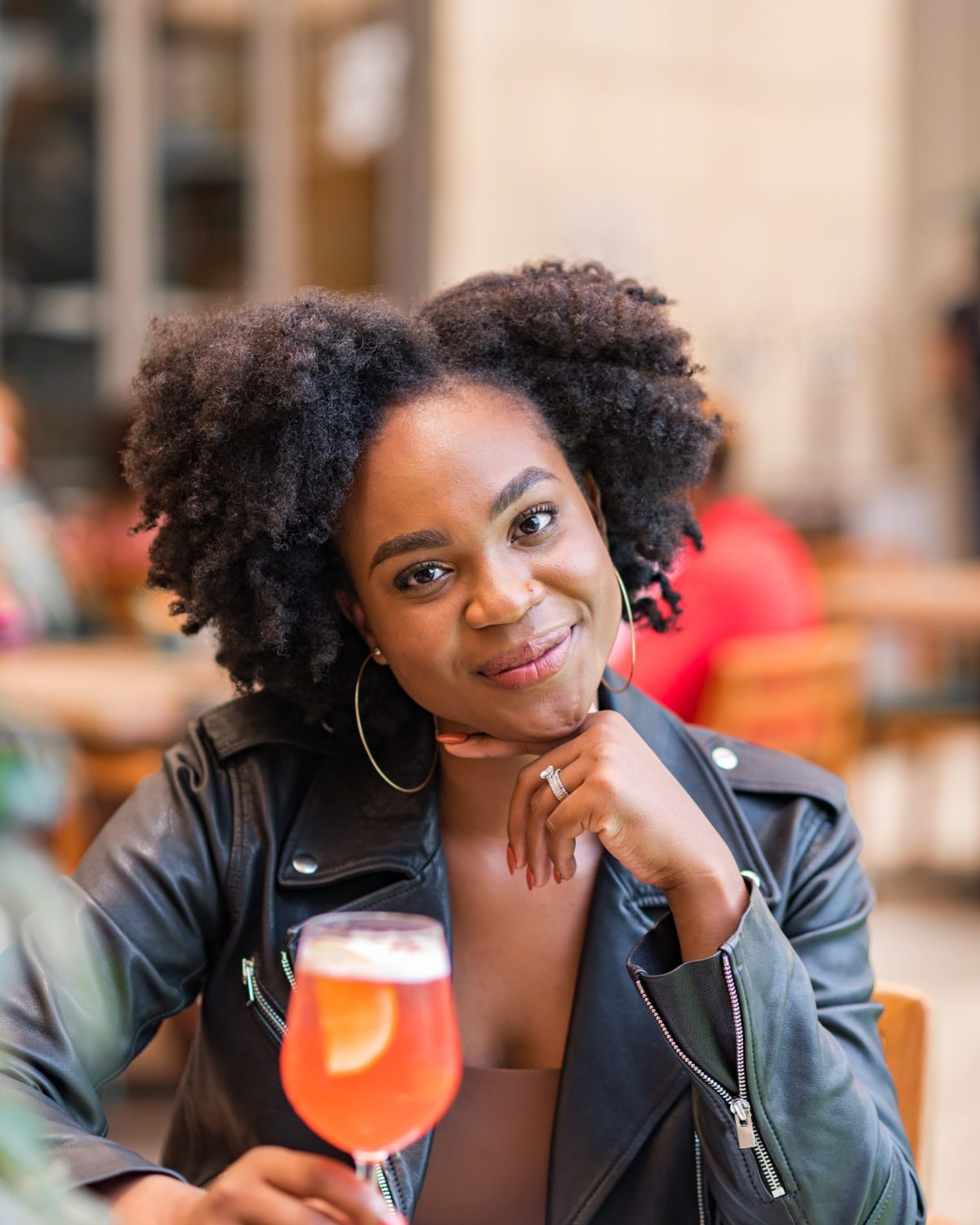 Ijeoma Kola at restaurant with cocktail, wearing leather jacket and black afro