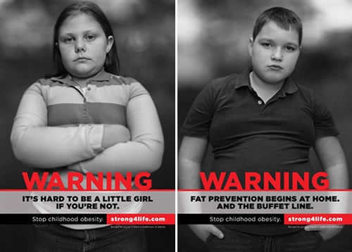 "This image combines two images, side by side. One is a fat young girl looking unhappy, with her arms crossed. The text reads ""WARNING: it's hard to be a littler girl if you're not. Stop childhood obesity. strong4life.com"" The other image shows a fat boy with an unhappy expression and his hands in his pockets, slouching. The text reads ""WARNING: fat prevention begins at home. And the buffet line. Stop childhood obesity. strong4life.com"""