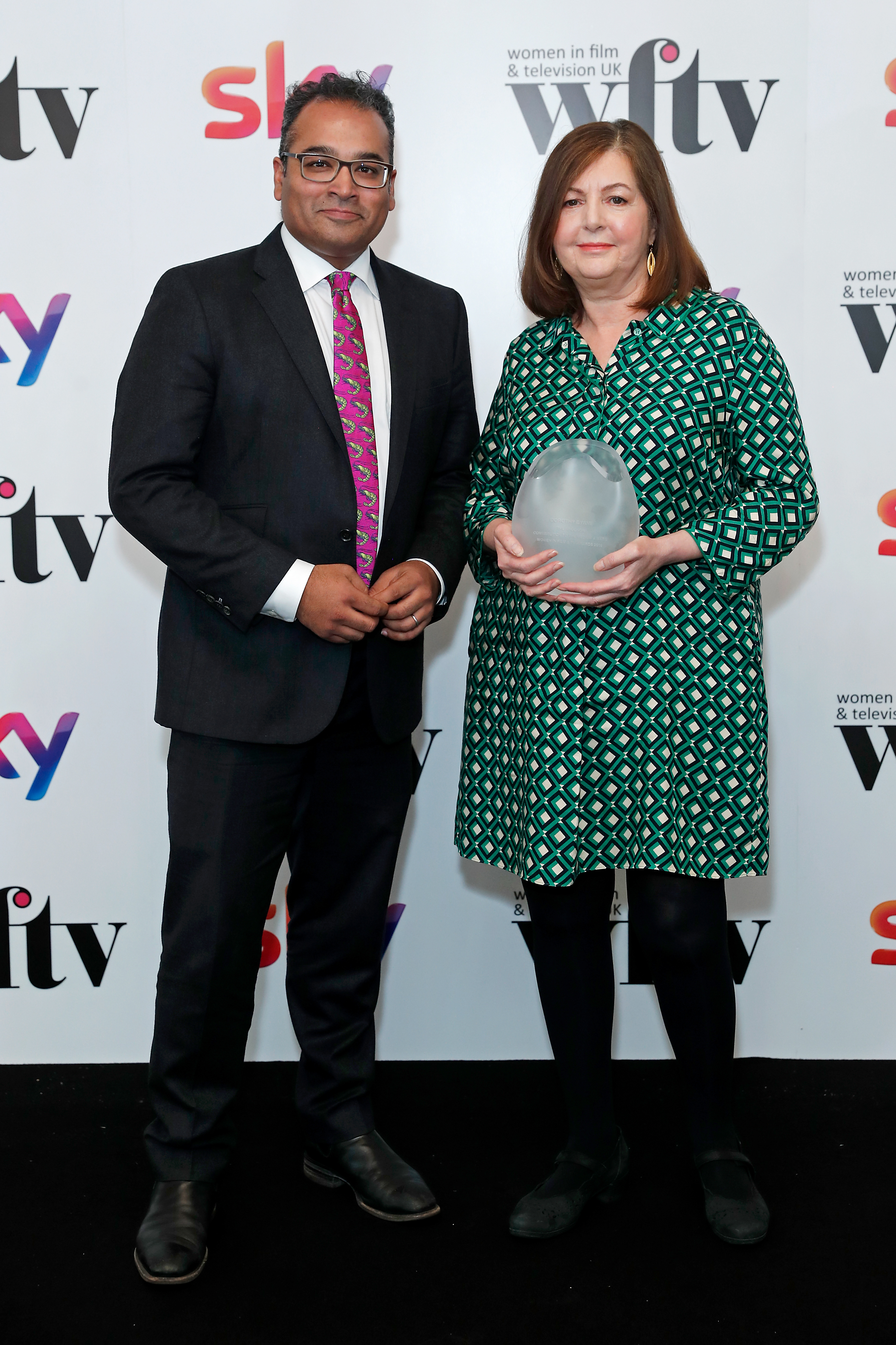 LONDON, ENGLAND - DECEMBER 06: Dorothy Byrne (R) winner of the Argonon Contribution to the Medium Award presented by Krishnan Guru- Murthy in the winners room at the Women in Film and TV Awards 2019 at Hilton Park Lane on December 06, 2019 in London, England. (Photo by David M. Benett/Dave Benett/Getty Images for Women in Film and TV)