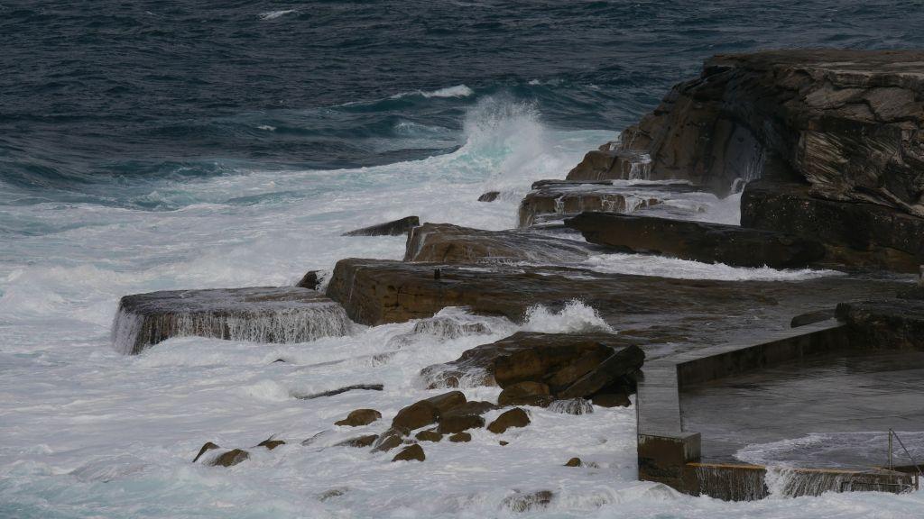 Blauwe zee met hoge golven die tegen de rotsen aanslaan