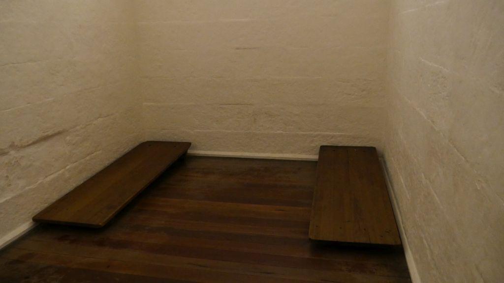 Een gevangeniscel met twee houten bedden