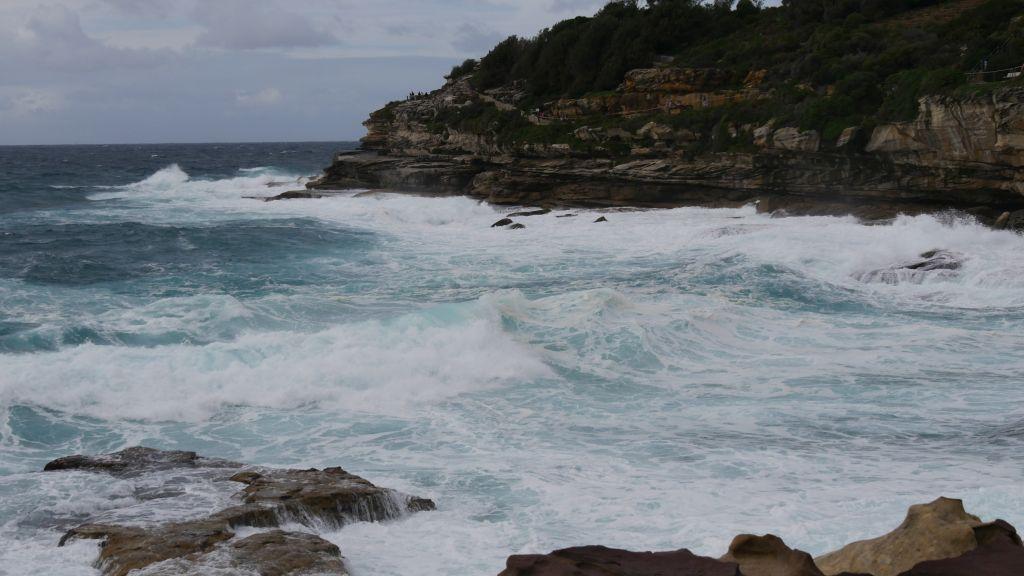 Blauwe zee met witte golven die tegen de rotsen aan kapotbreken