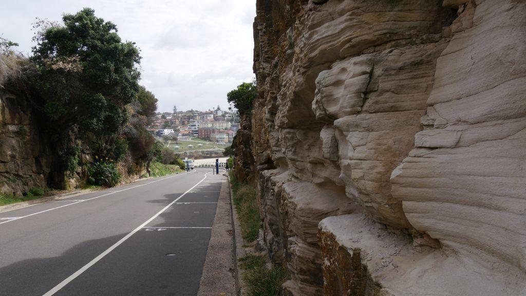 Doorgaande weg met aan de rechterkant een muur van steile rotsen en links bomen