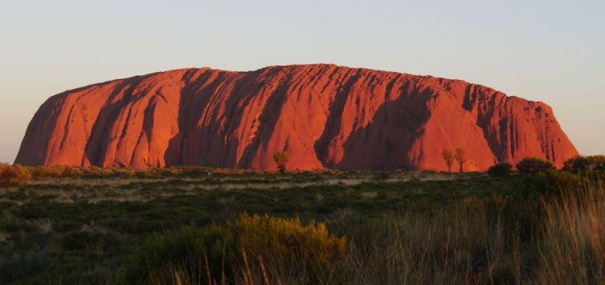 Uluru (Ayers Rock) tijdens de zonsondergang die roodgloeiend lijkt