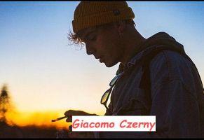 Giacomo Czerny nuovo tronista di Uomini e donne all'imbrunire mentre guarda il cellulare