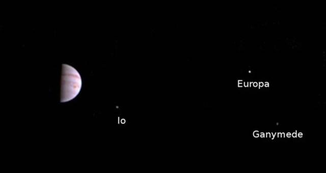 """Giove insieme a tre dei quattro satelliti """"Medicei"""", visti dalla sonda Juno in avvicinamento al sistema."""