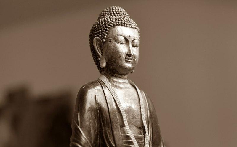 silver buddha statue in meditation