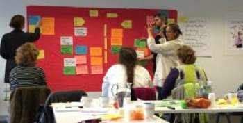 Participants on Illuma's Foundations of Facilitation training workshop working up their dynamic version of a Force Field Analysis is a practise session (2014)