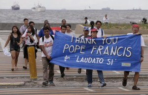 """Environmental activists carry a banner as they march towards a Roman Catholic church to coincide with Pope Francis' encyclical on climate change Thursday, June 18, 2015 in Manila, Philippines. In a high-level, 190-page document released Thursday, Francis describes ongoing human damage to nature as """"one small sign of the ethical, cultural and spiritual crisis of modernity."""" The solution, he says, will require self-sacrifice and a """"bold cultural revolution"""" worldwide. (ANSA/AP Photo/Bullit Marquez)"""