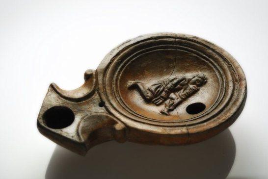 MASDA_003 Lucerna con pugile a riposo raffigurato dalla necropoli romana