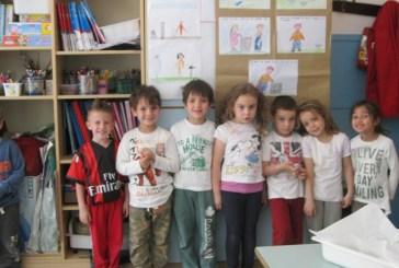 Gli alunni della scuola dell'infanzia felici consegnano vari sacchi di tappi per il riciclo