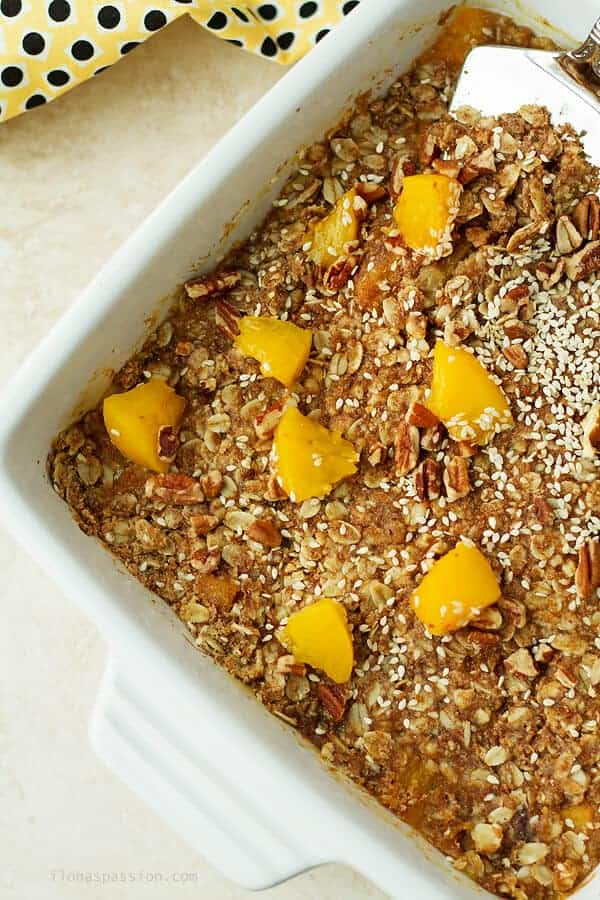 An overhead photo of peach crumble in white baking pan. Baked crumble with some canned peaches on top.