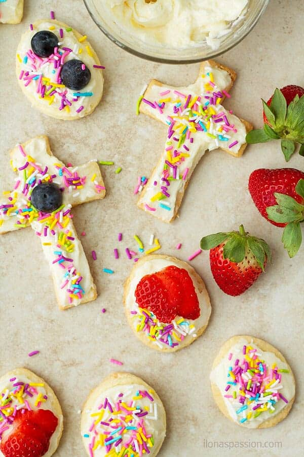 Cross, egg cookies decorated with fresh strawberries, blueberries and sprinkles.