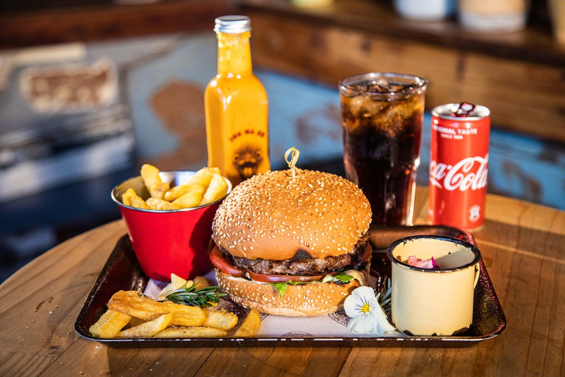 Burger with coleslaw, fries, and brandy & coke