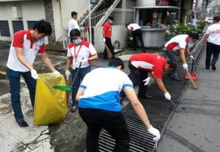 Employee-volunteers from Ajinomoto Philippines Corporation work in teams as they clean surrounding areas of their office during the Smile Earth! Clean Up our Earth Together Day.