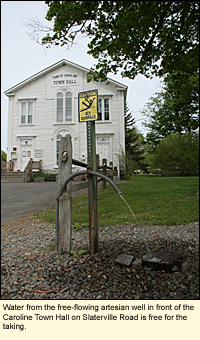 Water from the free-flowing artesian well in front of the Caroline Town Hall on Slaterville Road is free for the taking.