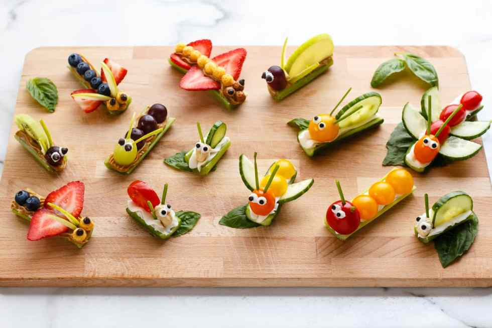 Fruit and vegetable bug snacks arranged on a wood board.