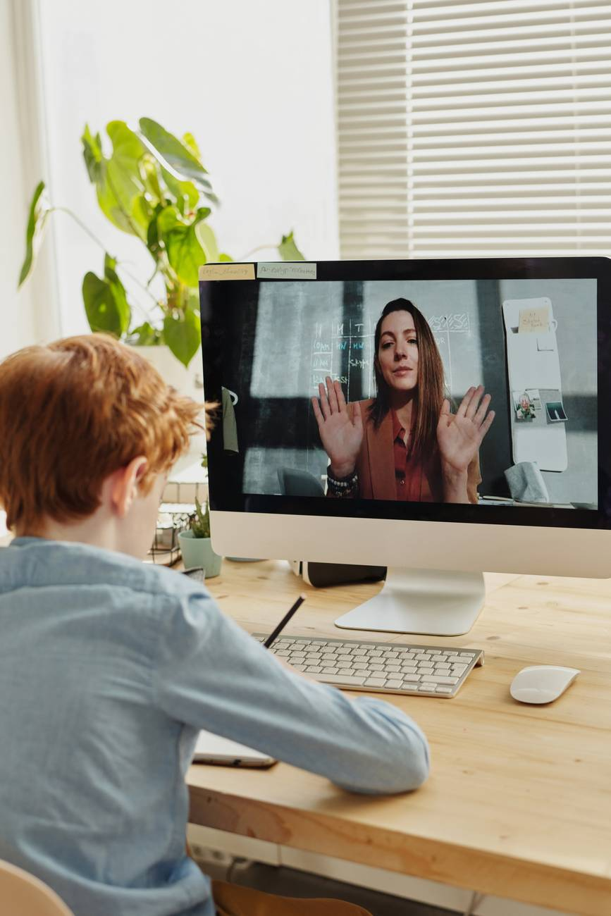 photo of boy video calling with a woman through imac