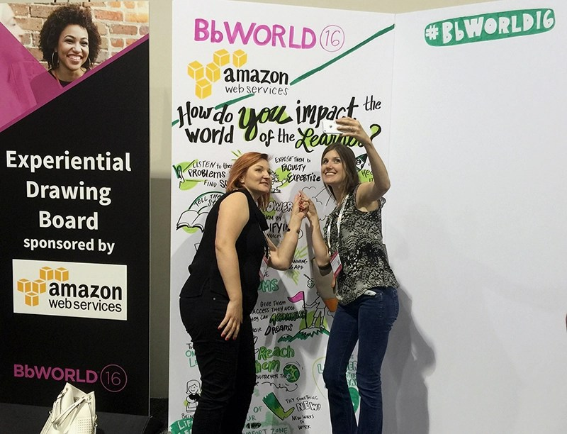 "Bb World 2016 conference female attendees taking a selfie with their contribution to ImageThink's social listening wall. The question is ""How Do You Impact the World of the Learner?"" Their answer is ""Expose them to faculty expertise"". The graphic recording behind them showcases conference engagement in answering the education question."