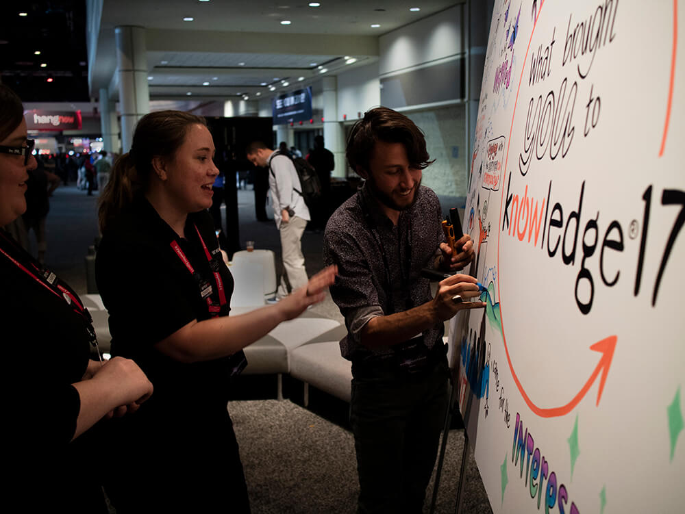 a graphic recorder from imagethink draws on a whiteboard at a technology conference