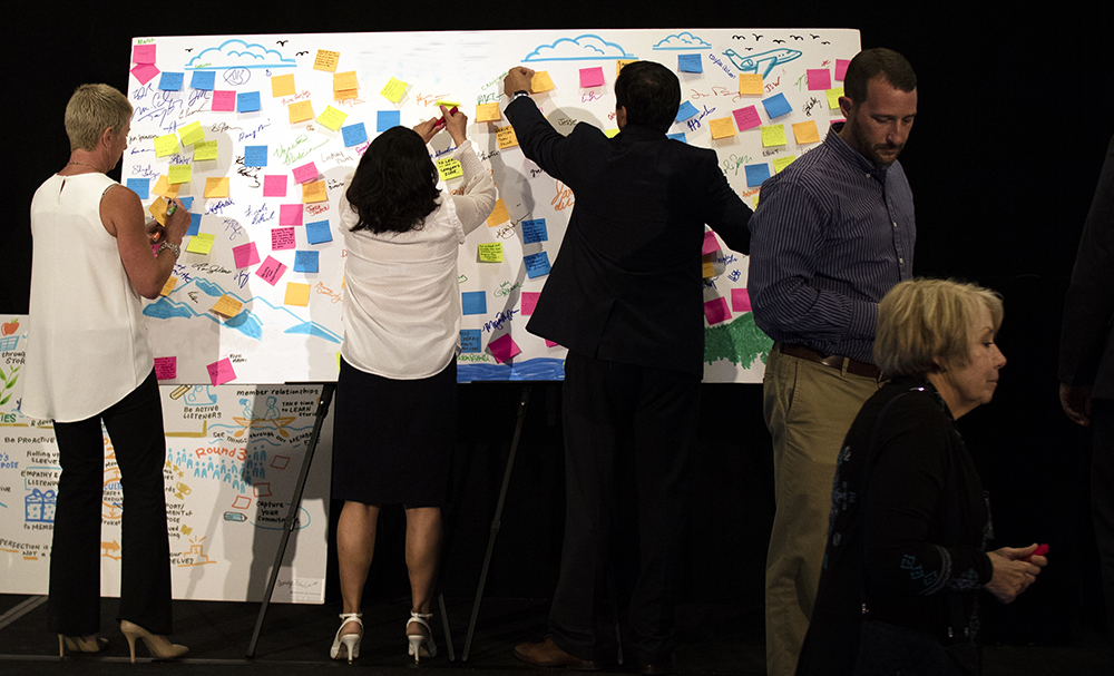 meeting attendees use a whiteboard illustration from imagethink to vote on new ideas and prioritize strategies.
