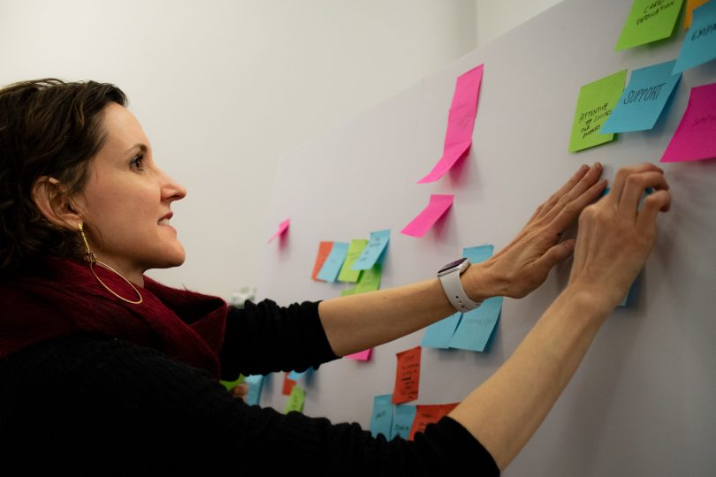 ImageThink's founder and CEO, Nora Herting, placing sticky notes on a board while facillitating a brainstorm session