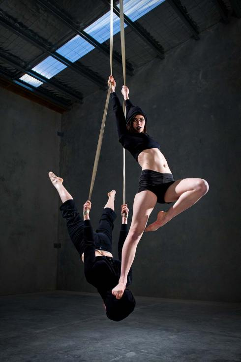 Promotional and advertising photography of professional circus arts performers on straps in a warehouse