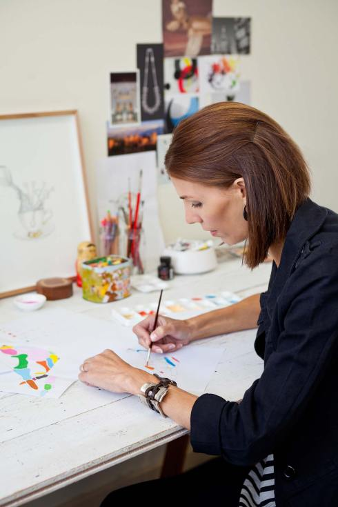 Clean and natural editorial portrait of Melanie Miles an illustrator and artist at work in her studio.