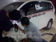 Karyawan IMAGI CS sedang memasang sticker striping pada Mobil Toyota Avanza.
