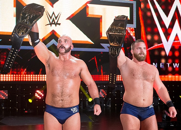 The Revival hold their championship belts aloft