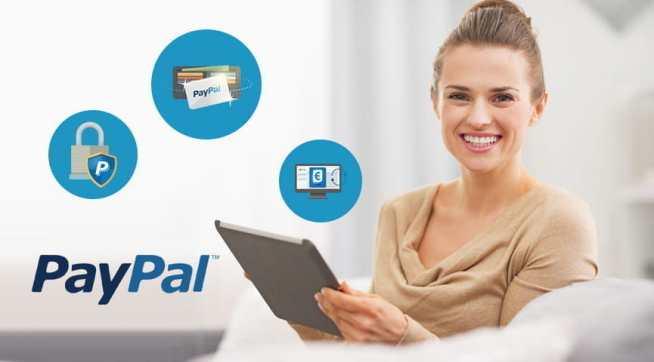 Una ragazza con in mano un tablet e il logo PayPal