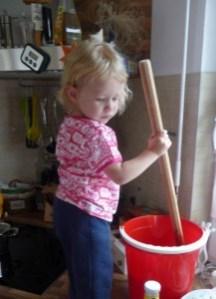 Tochter beim Honig rühren, Tochter beim Rühren von Flüssigfutter für Bienen