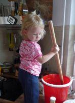Tochter beim Honig rühren, Bienenfuttersirup herstellen