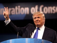 Donald Trump holds up right hand showing peace sign