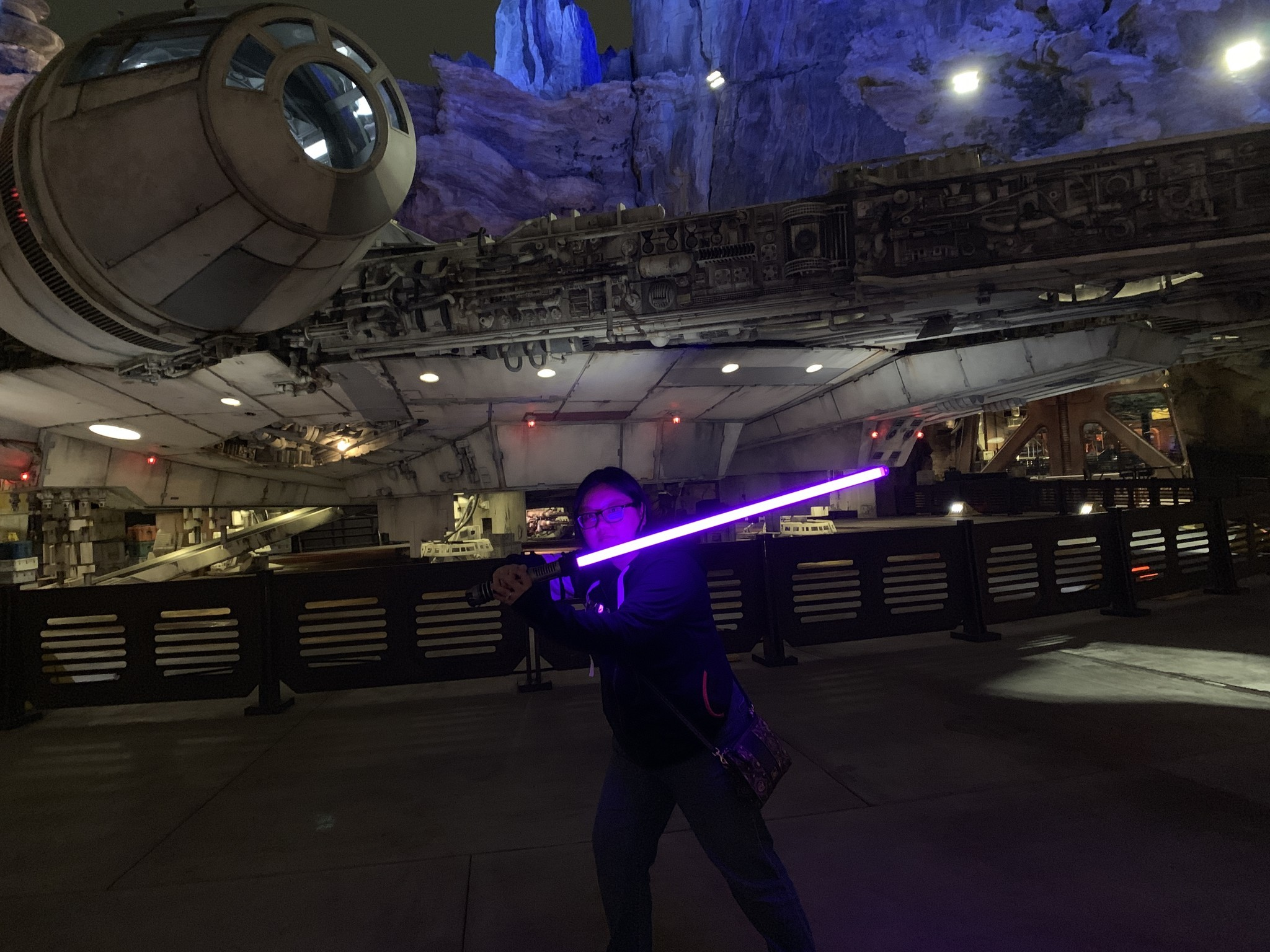 hight resolution of christine chan holds her violet lightsaber in front of the millennium falcon