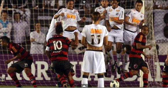 Ronaldinho cobra a falta por debaixo da barreira...