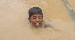 A boy swims as he was crossing the floded area caused by Sirisiya River in Ramghaduwa , Parsa District , Nepal