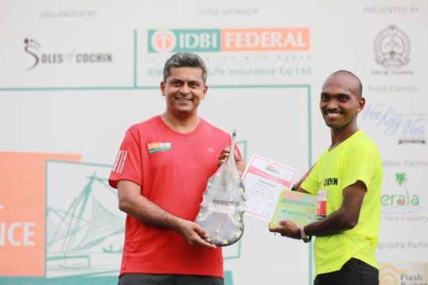 Karthik Raman, CMO, IDBI Federal Life Insurance felicitating the winner of the Full Marathon, Mahesh P S at the IDBI Federal Life Insurance Spice Coast Marathon 2018