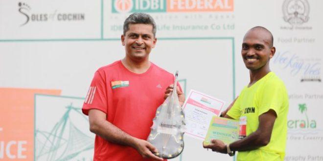 Karthik Raman, CMO, IDBI Federal Life Insurance felicitating the winner of the Full Marathon, Mahesh P S at the IDBI Federal Life Insurance Spice Coast Marathon 2018