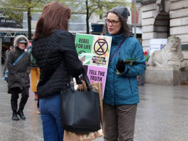 A campaigner informs a pedestrian about extinction level threats [image by: kthtrnr/Flickr]