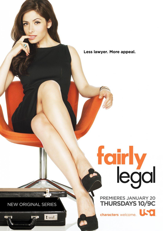 Sarah Shahi als Kate Reed sitzt auf einem orangefarbenen Stuhl, Aktenkoffer zu ihren Füßen. Provozierender Blick