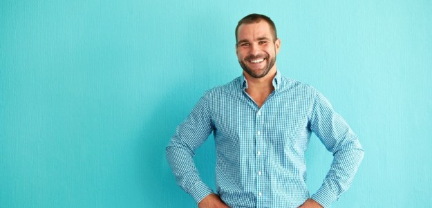 Happy man in front of turquoise wall
