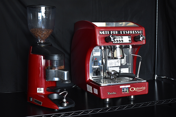 A red espresso grinder and a red espresso machine with dark background