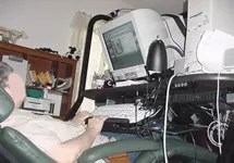 Client using a computer from a reclined position. The keyboard and monitor are on a special type of desk to allow her to have these items in the proper position when reclined.