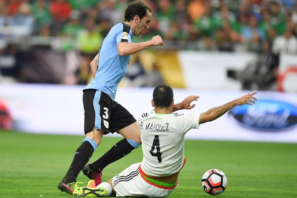 Rafael Marquez of Mexico slide tackles Uruguay player, Diego Godin during the first round of match play.
