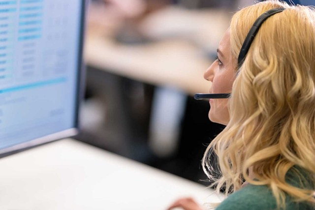 Adult woman with a headset, with a microphone, using a computer while talking to a customer in a call center.
