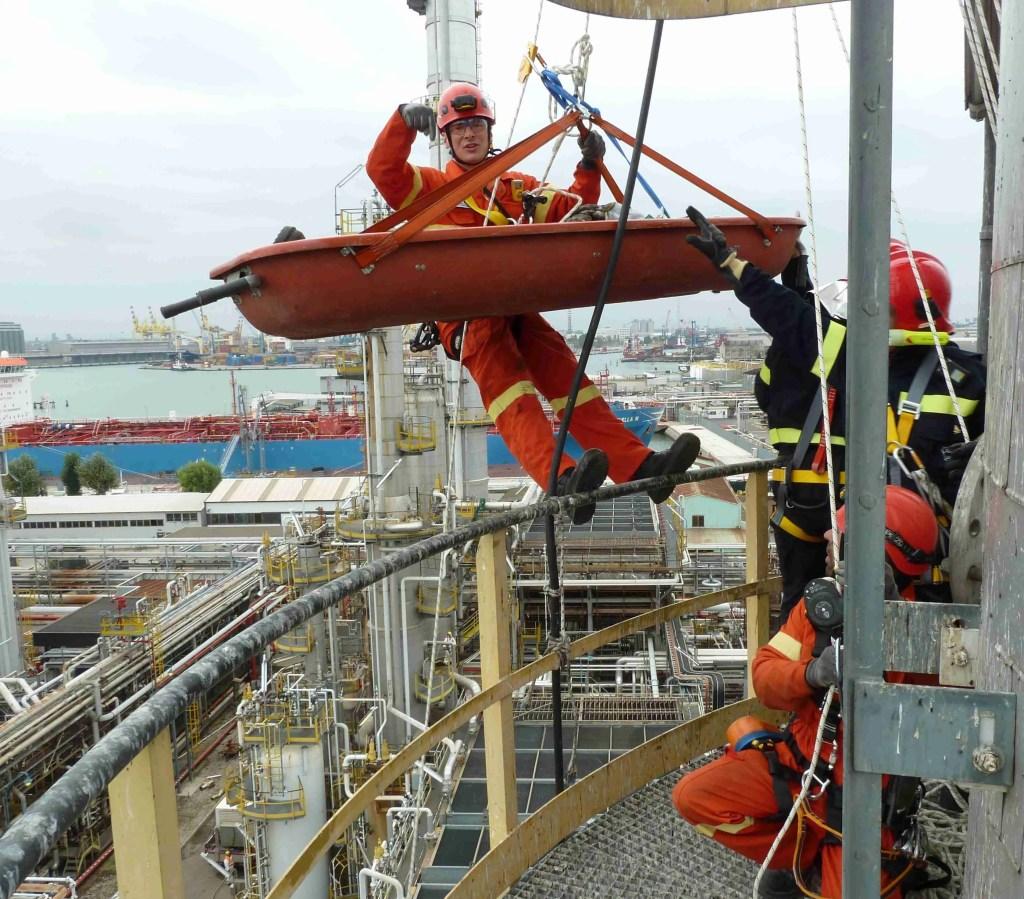 operatore accompagna ferito in barella toboga giù da un torre di raffinazione durante una esercitazione soccorso e recupero spazi confinati