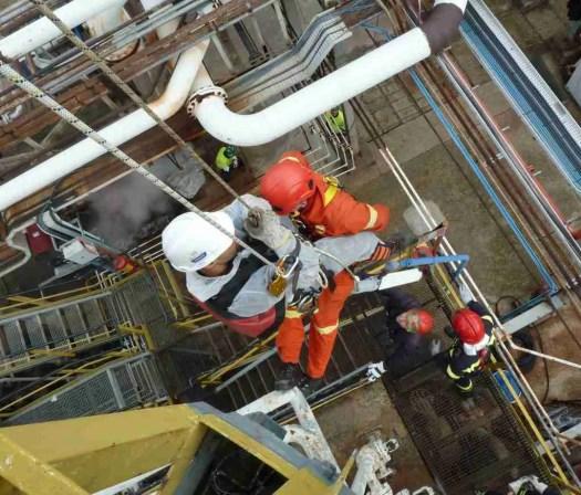 Operatore accompagna ferito in triangolo di soccorso giù da un torre di raffinazione durante una esercitazione soccorso e recupero